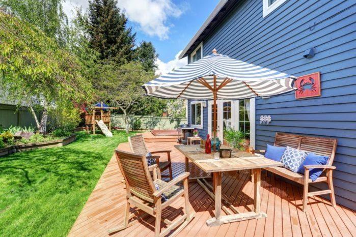 Wooden Walkout Deck In The Backyard Garden Of Blue Siding House